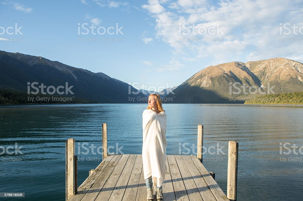 Woman stands on lake pier at sunrise stock photo