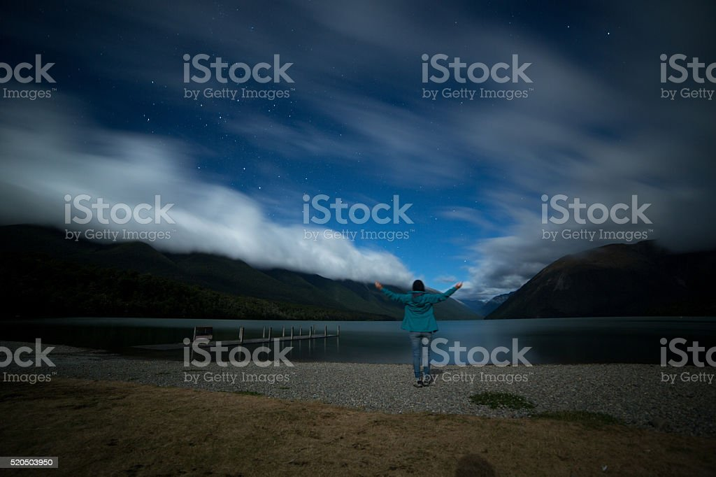 Woman stands on lake shore at night, arms outstretched stock photo