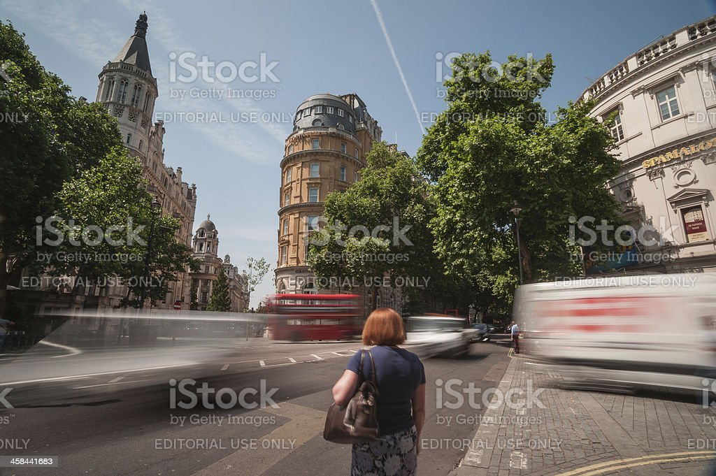Woman stands waiting at busy London intersection stock photo