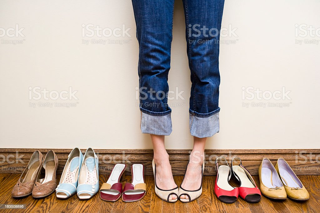Woman stands wearing heels with her collection of Shoes royalty-free stock photo