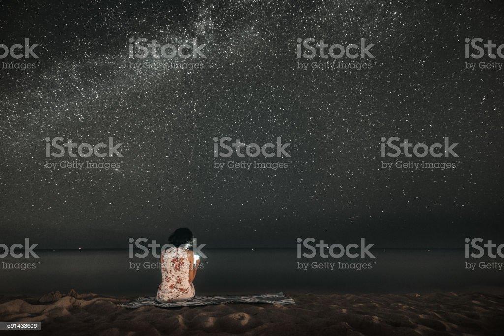 Woman Stargazing on the Beach stock photo