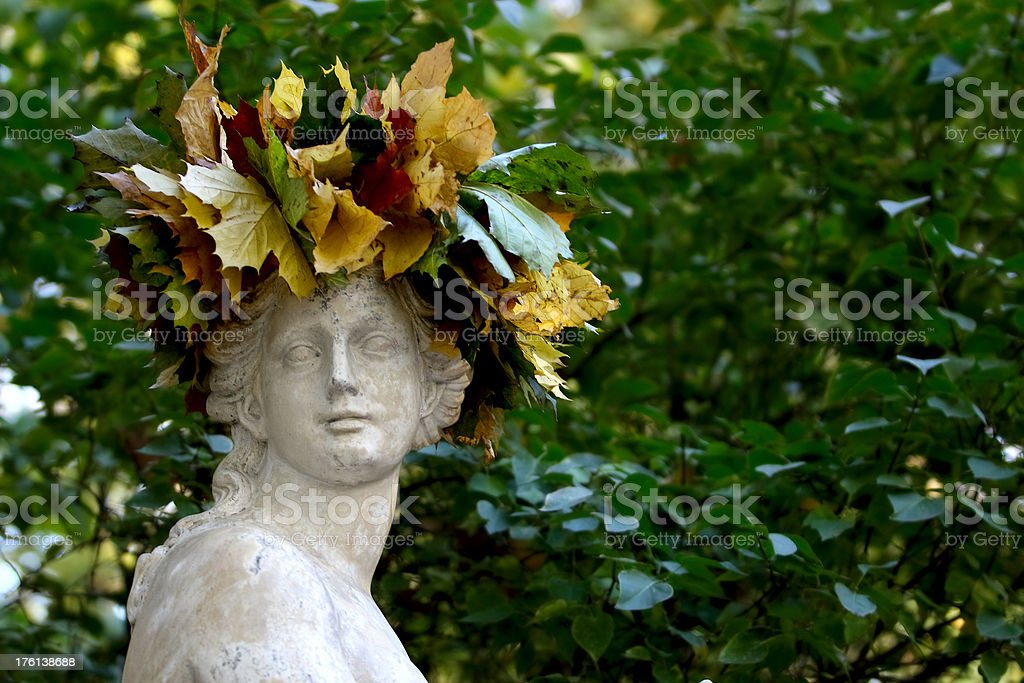 Woman statue in wreath made of colorful autumn leaves royalty-free stock photo