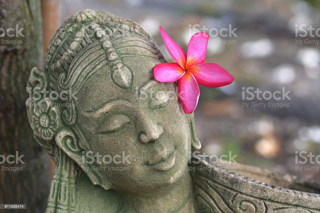 woman statue with red flower in her hair stock photo