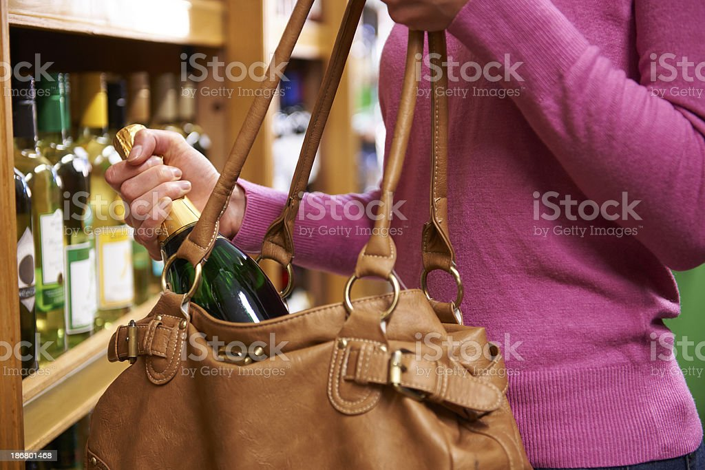 Woman Stealing Bottle Of Wine From Supermarket stock photo