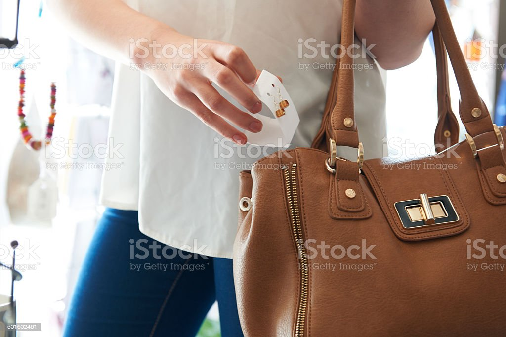 Woman Stealing Jewellery From Shop stock photo