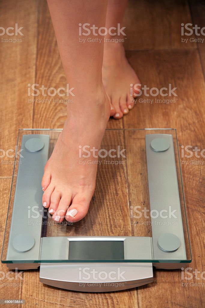 Woman stepping on scale. stock photo