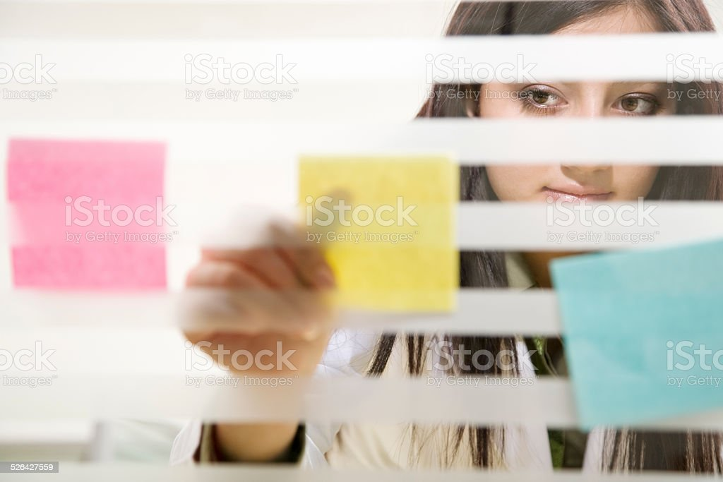 Woman Sticking Notes To Office Window stock photo