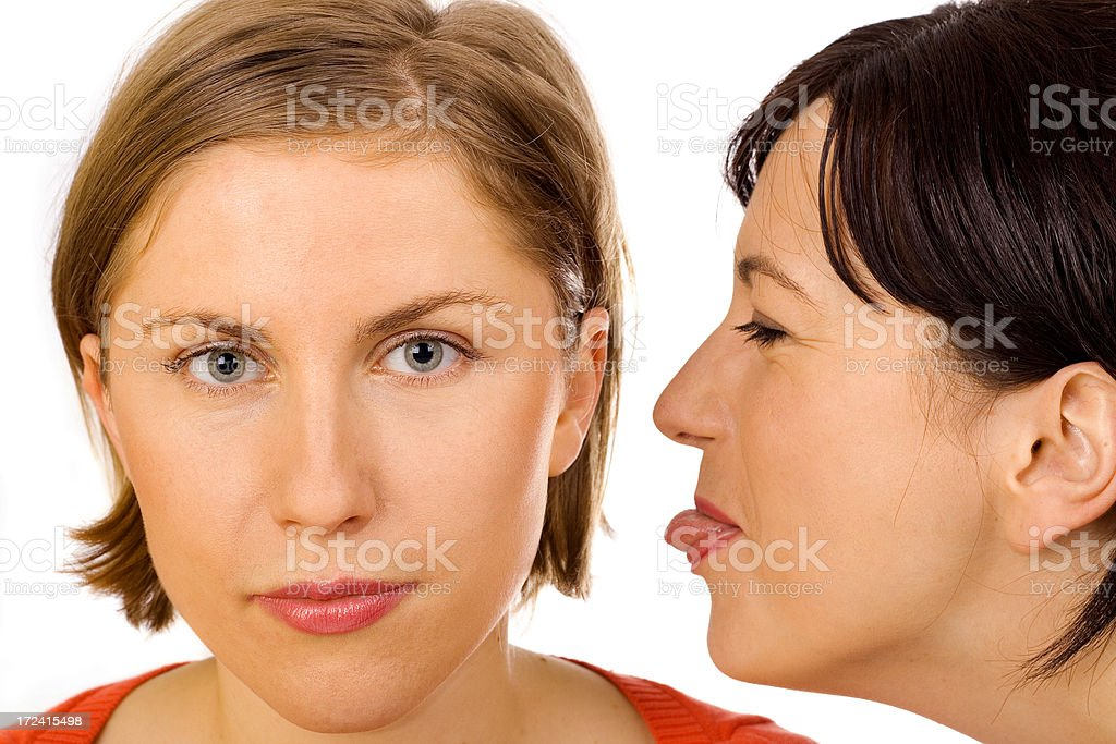 Woman sticking out  tongue to her friend's ear royalty-free stock photo