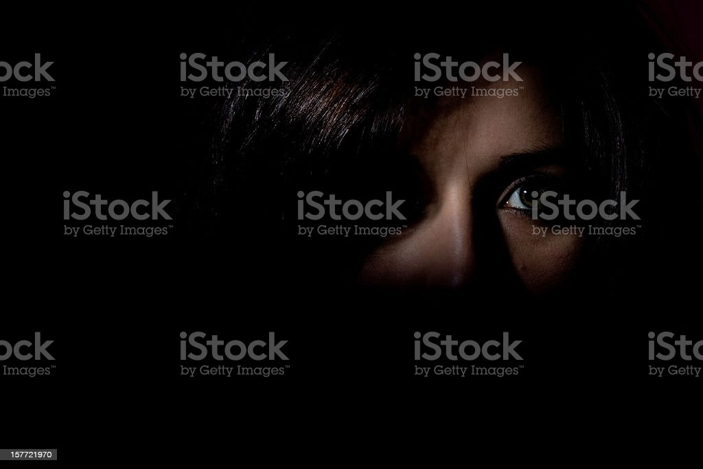Woman stood in the dark showing half her face looking scared stock photo