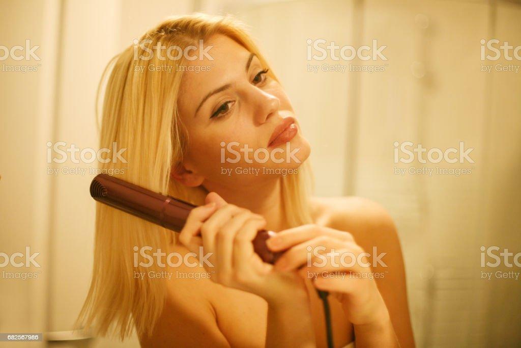 Woman straightening hair with straightened. Mirror reflection of woman  straightening hair with straightened stock photo