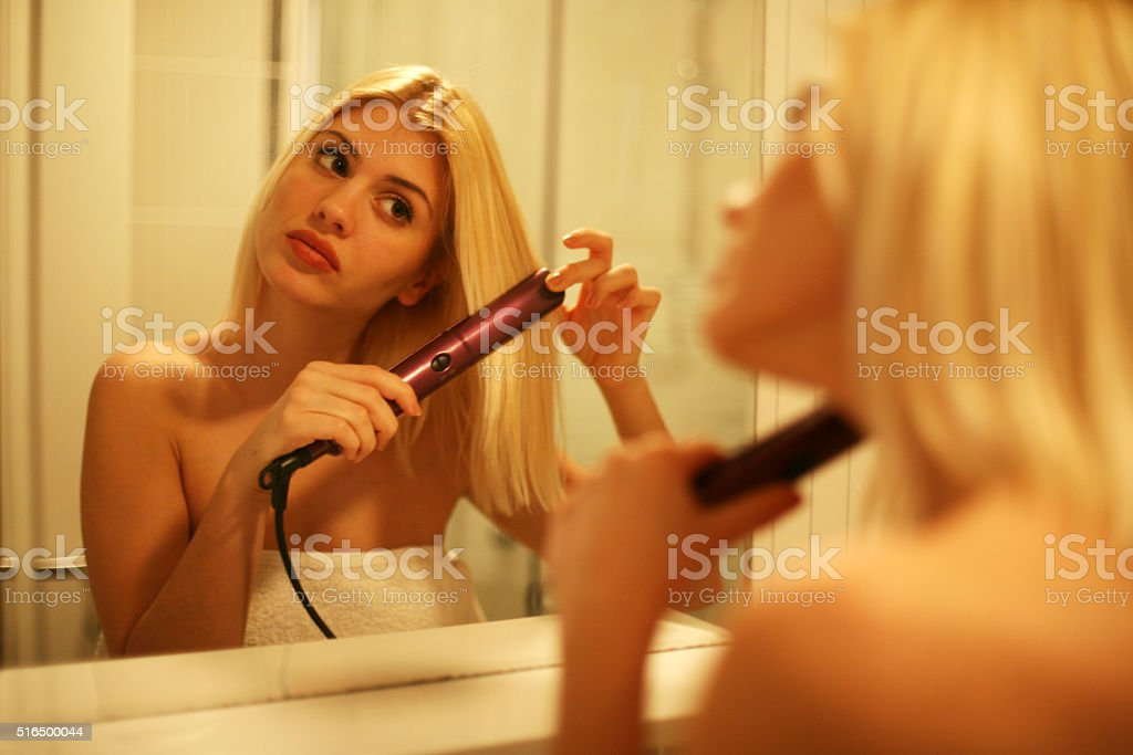 Woman straightening hair with straightener. stock photo