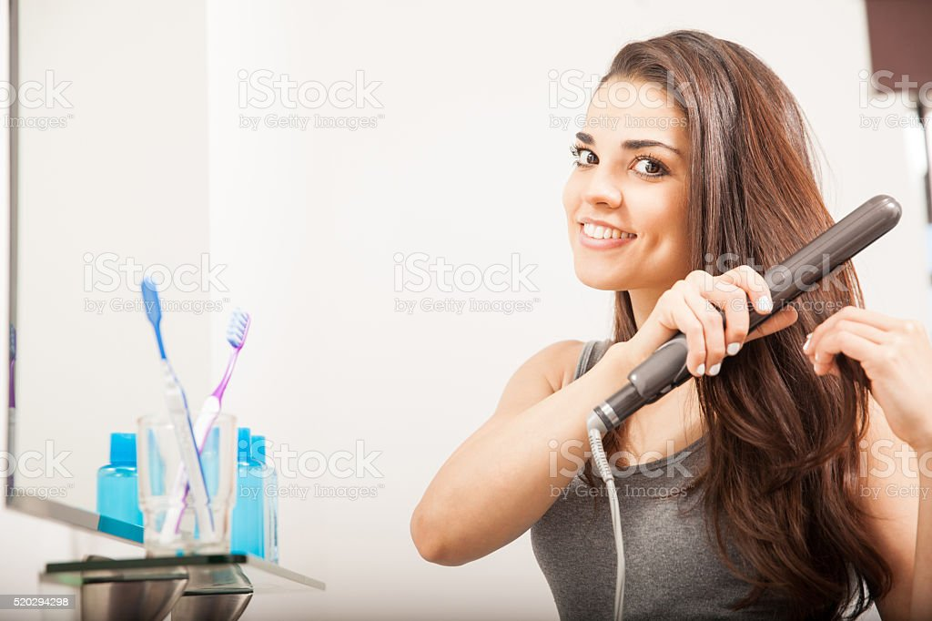 Woman straightening her hair with iron stock photo