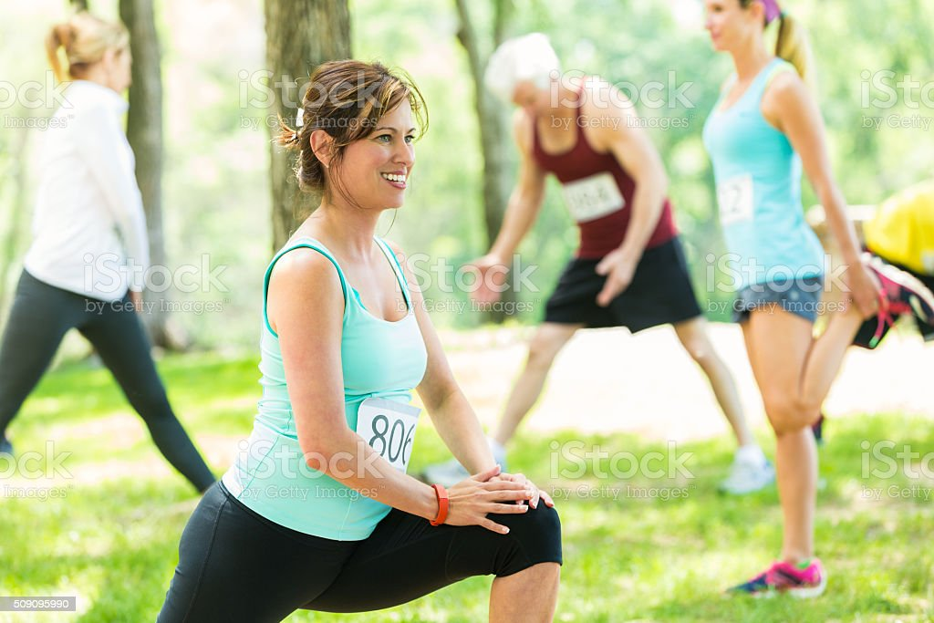 Woman stretches before 5k race stock photo