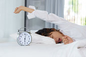 Woman stretching and yawning while waking up in the morning