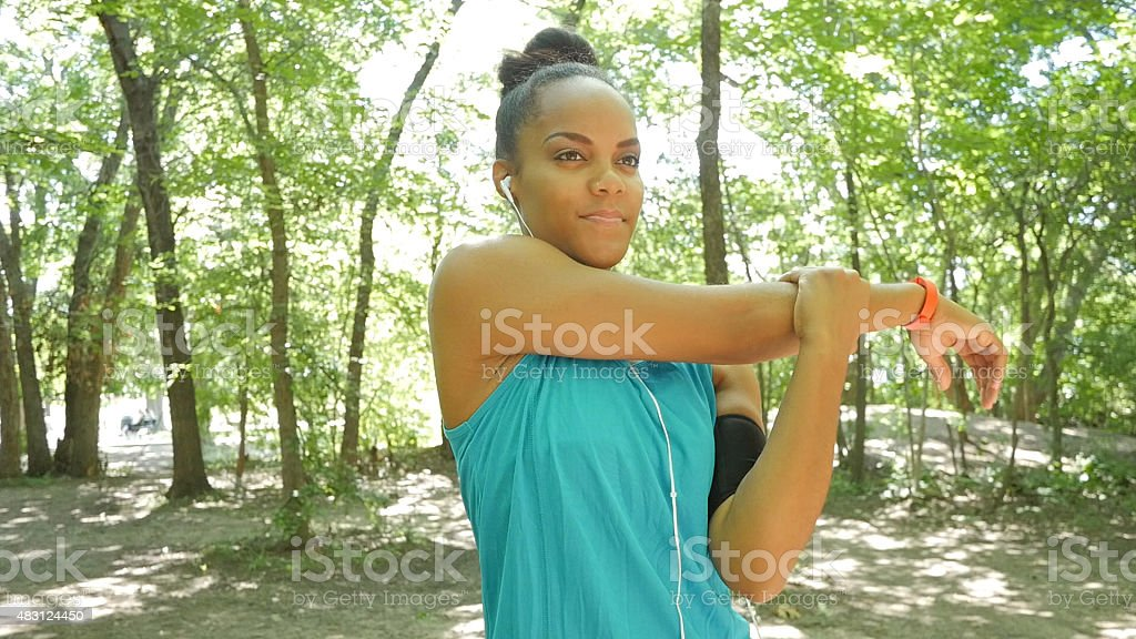 Woman stretching arms before running off road during workout stock photo