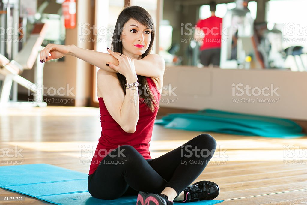 Woman stretching arms in sports club stock photo