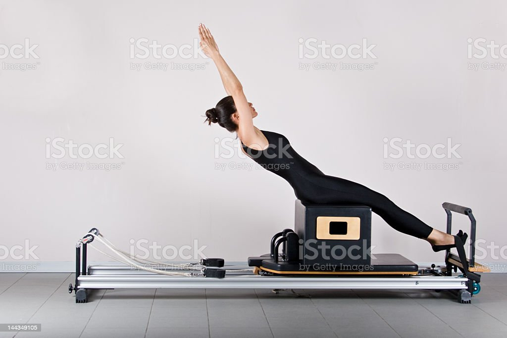 Woman stretching backward on exercise machine royalty-free stock photo