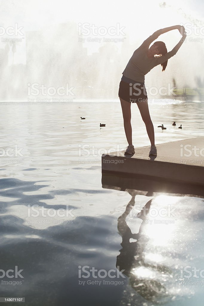 Woman stretching by still lake royalty-free stock photo