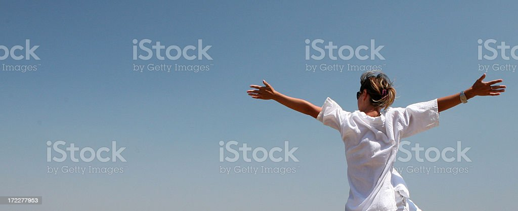 A woman stretching her arms in freedom stock photo