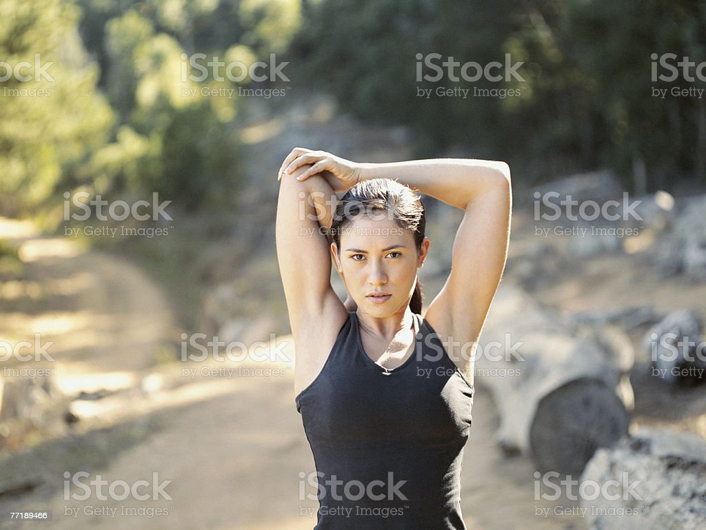 A woman stretching her arms out in the woods royalty-free stock photo