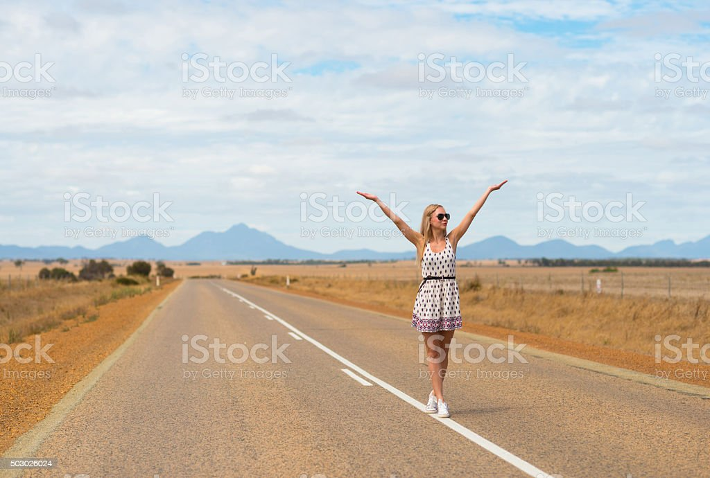Woman stretching her hands in the air in Australian outback stock photo