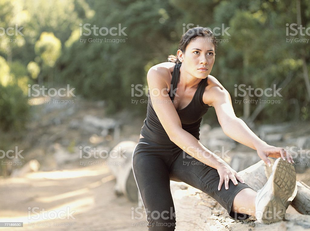 A woman stretching her legs in the woods royalty-free stock photo