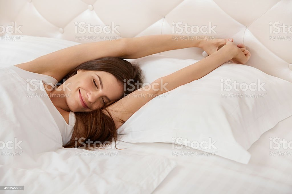 Woman stretching in bed. Girl Waking Up in The Morning stock photo