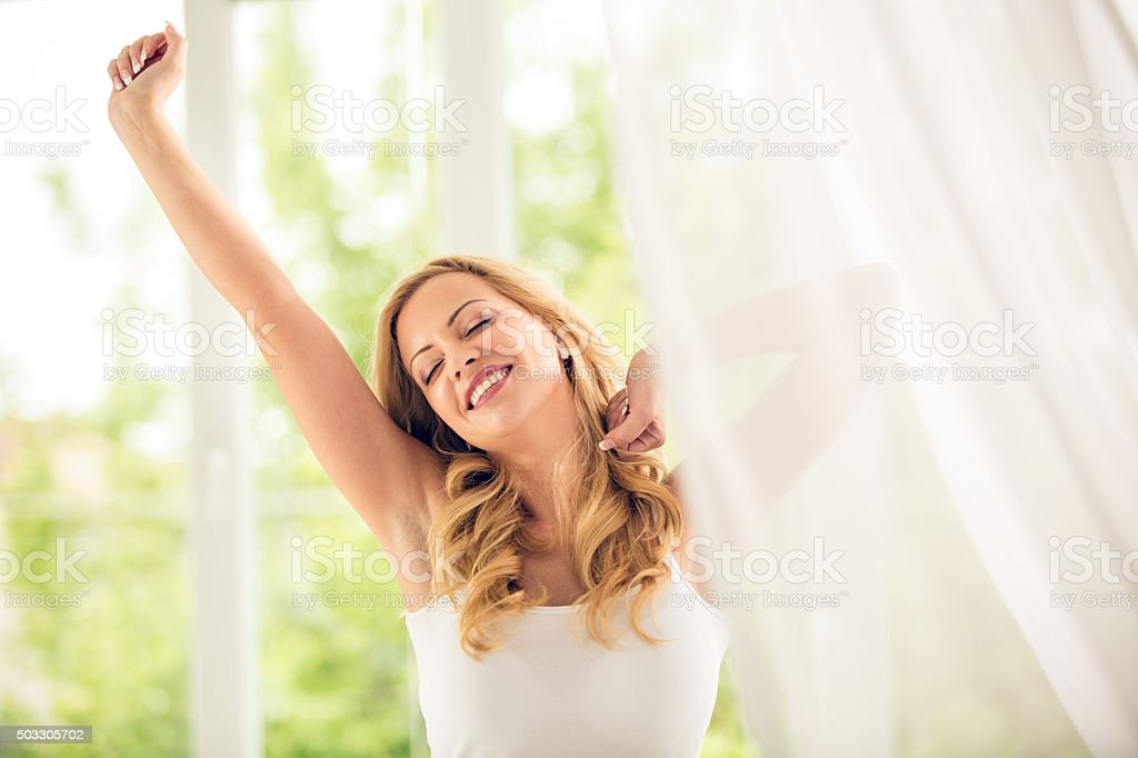 Woman stretching in bed stock photo