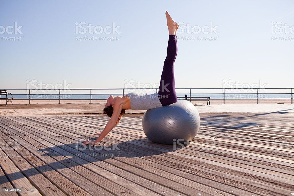 Woman stretching on exercise ball on promenade stock photo