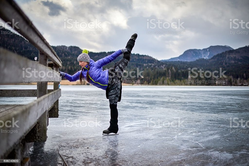 Woman stretching on the frozen lake stock photo