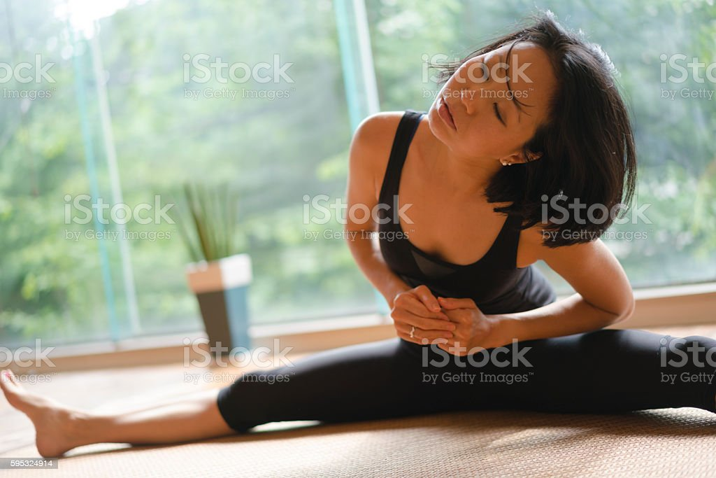Woman stretching while doing splits in yoga gym stock photo