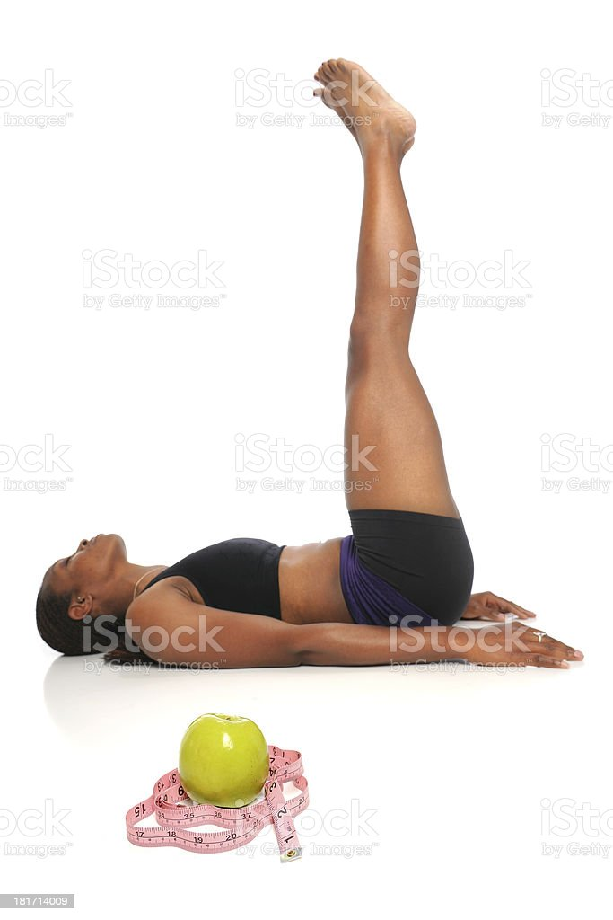 Woman Stretching With Apple and Tape in Foreground royalty-free stock photo