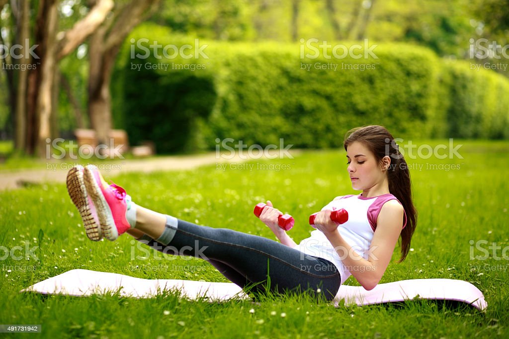 Woman stretching with dumbbells, fitness exercises in park stock photo