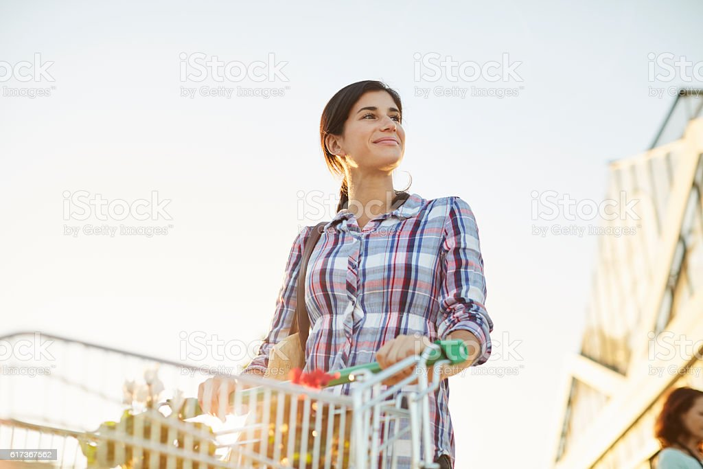 Woman strolling with a cart in a garden center. stock photo
