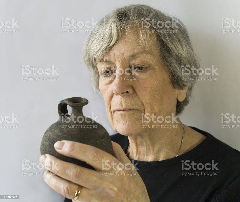 Woman studying antiquarian pot. stock photo