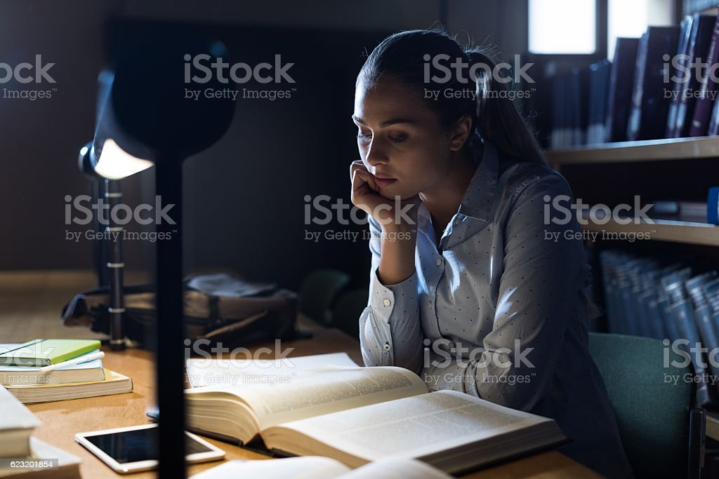 Woman studying late at night stock photo