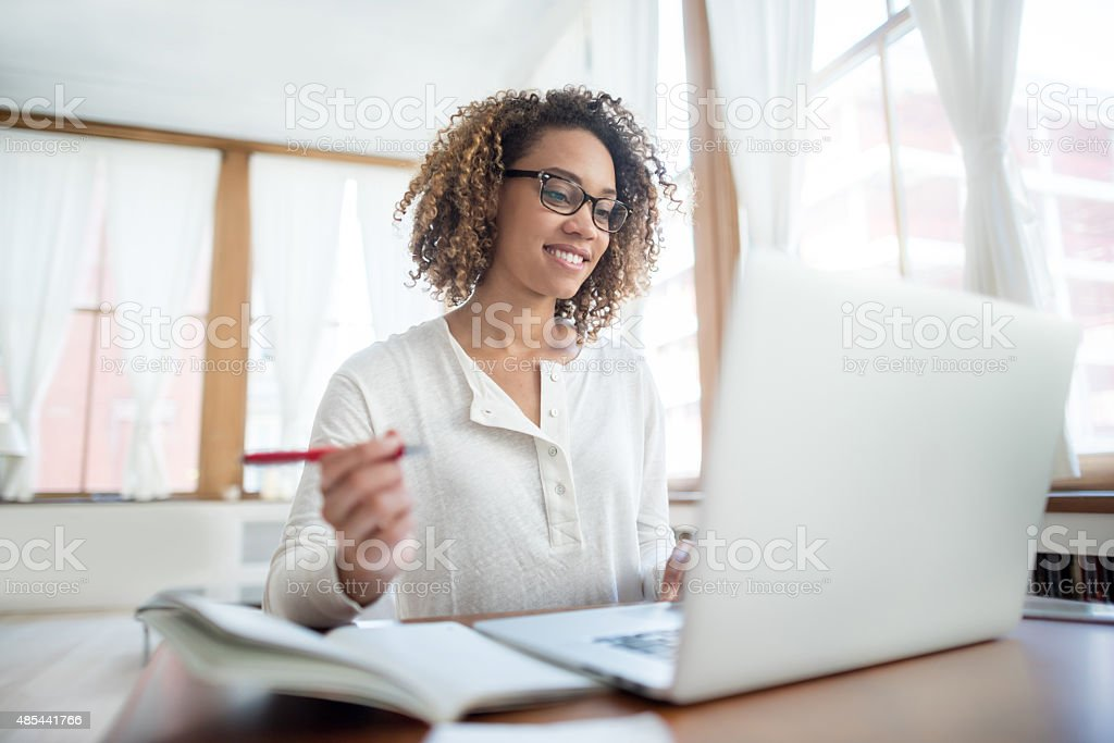 Woman studying online at home stock photo