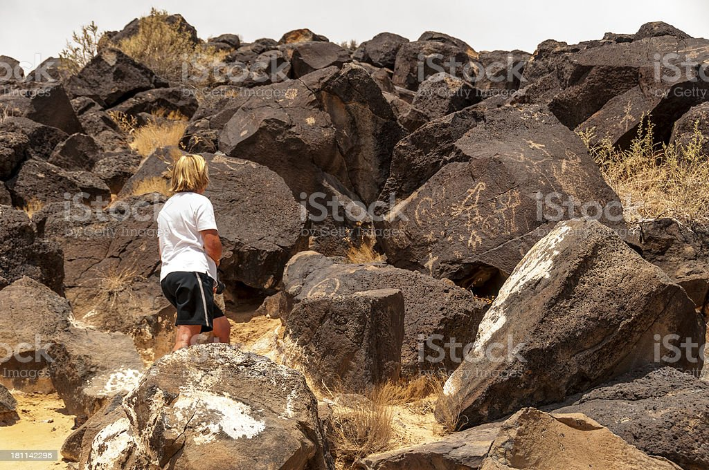 Woman Studying Petroglyphs stock photo