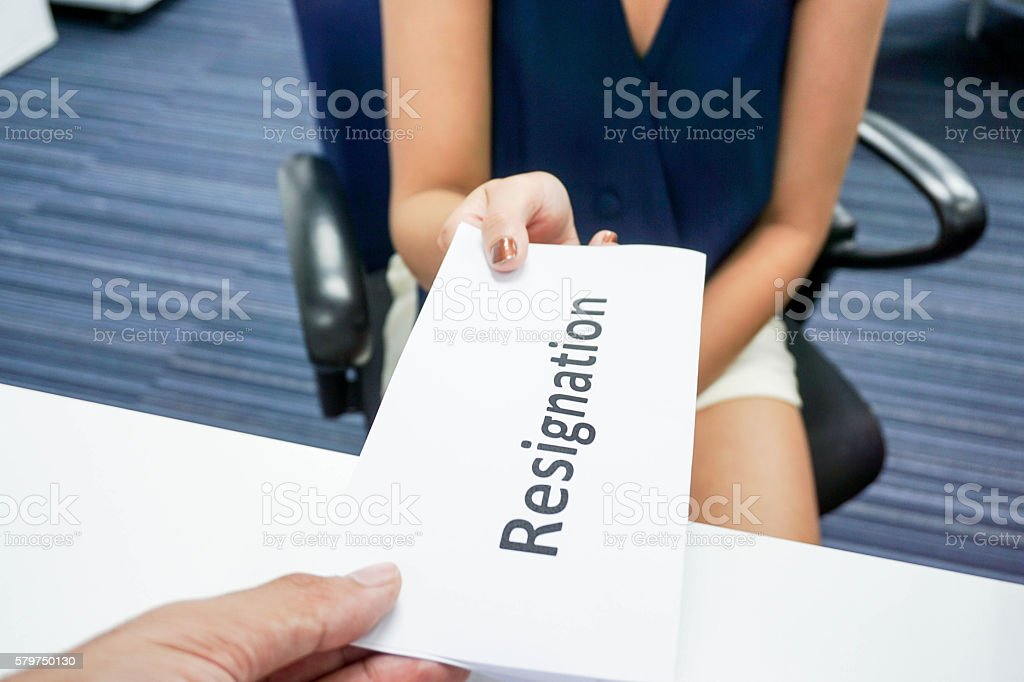 woman submit a resignation letter to her boss stock photo