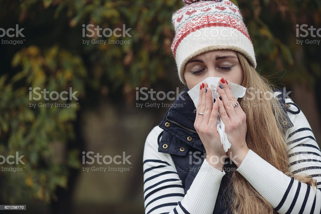 Woman Suffering From Cold outdoor with Tissue stock photo