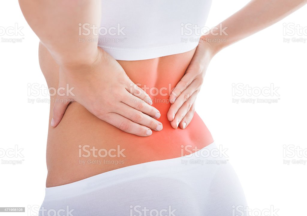 Woman suffering from lower back pain in white stock photo