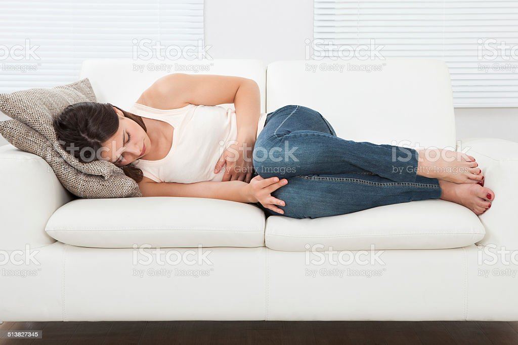 Woman Suffering From Stomachache On Sofa stock photo