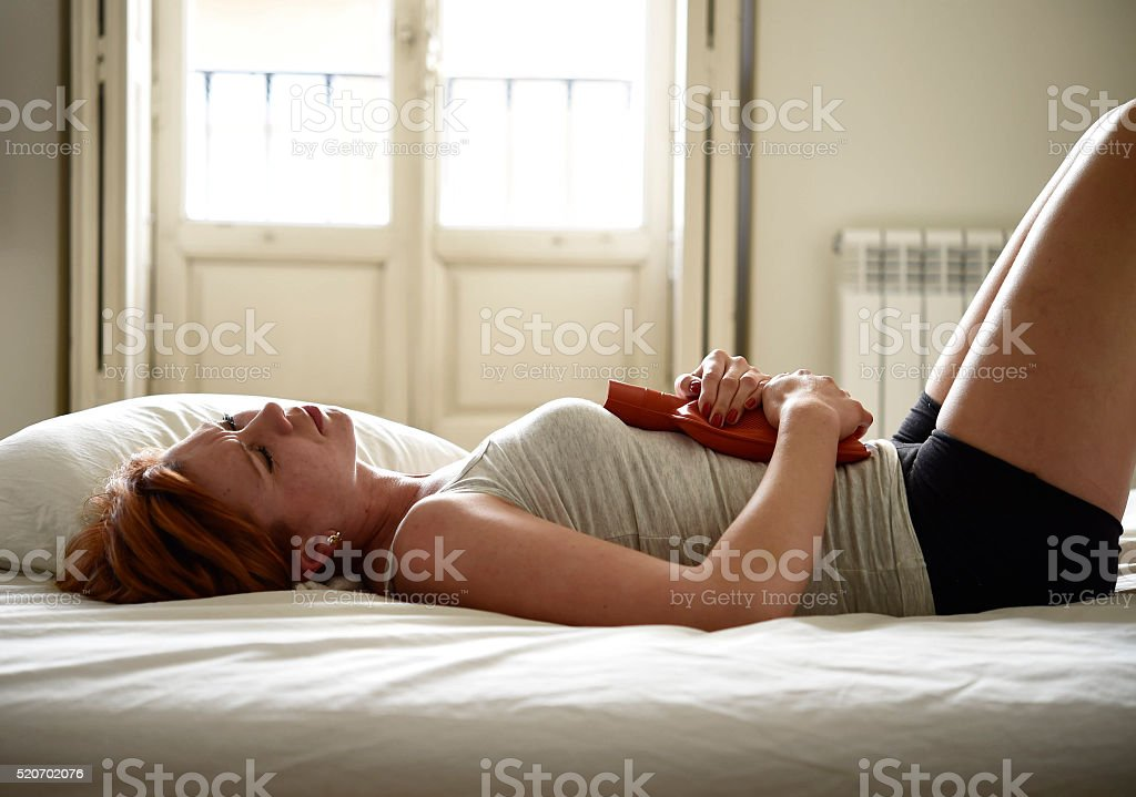 young beautiful woman suffering stomach cramps on belly holding with...