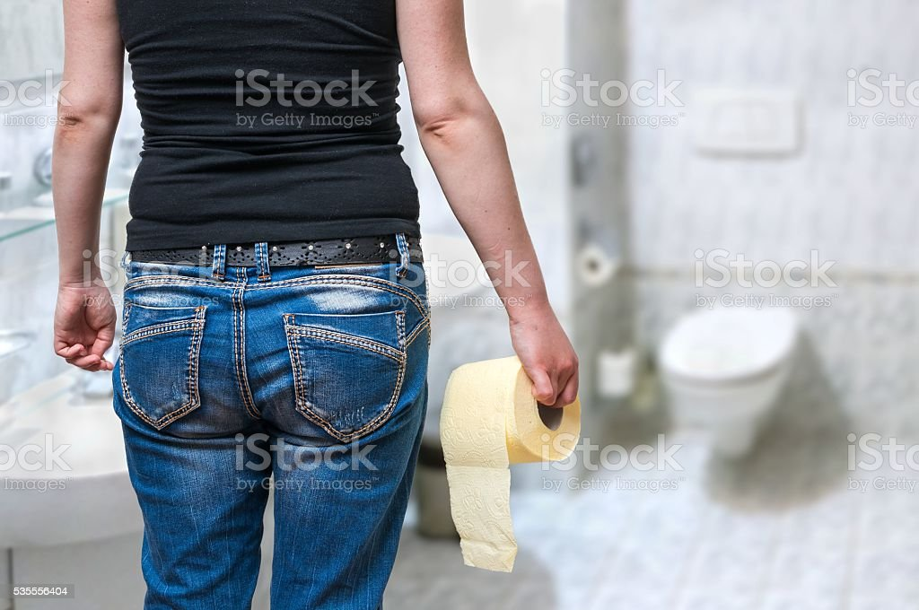 Woman suffers from diarrhea holds toilet paper in hand. stock photo