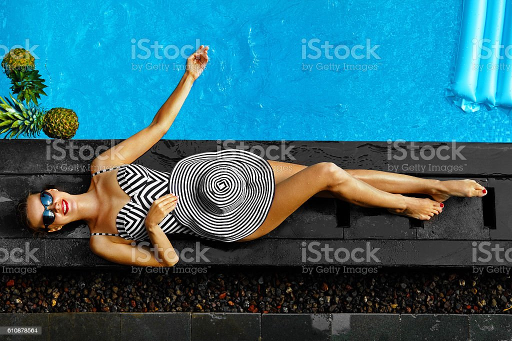 Woman Summer Fashion. Sexy Girl Sunbathing By Swimming Pool. Beaty stock photo