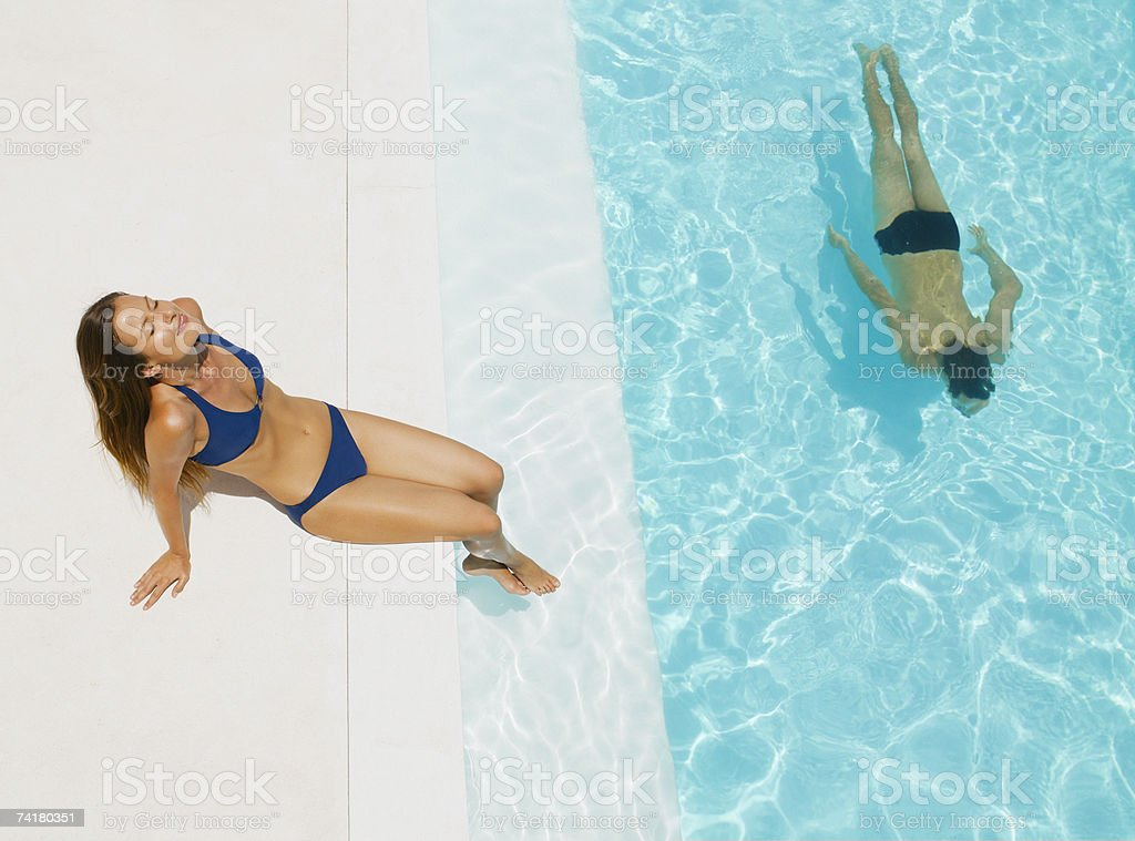 Woman sunbathing and man swimming in pool royalty-free stock photo