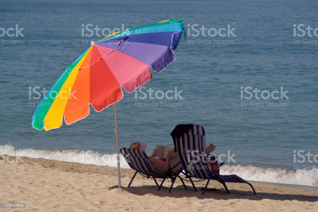 Woman Sunbathing and Reading in Beach Chair Under Umbrella royalty-free stock photo