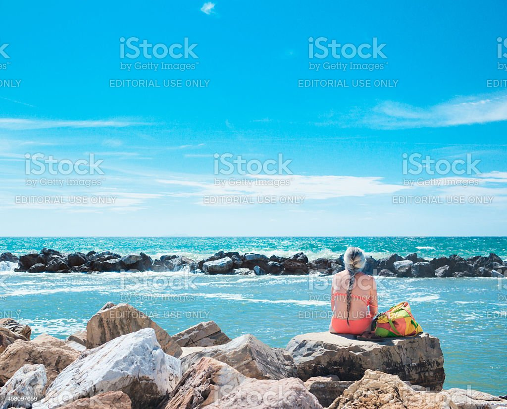 Woman sunbathing at the sea in Tuscany royalty-free stock photo