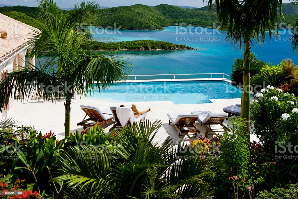 woman sunbathing by a pool on the Caribbean vacation royalty-free stock photo