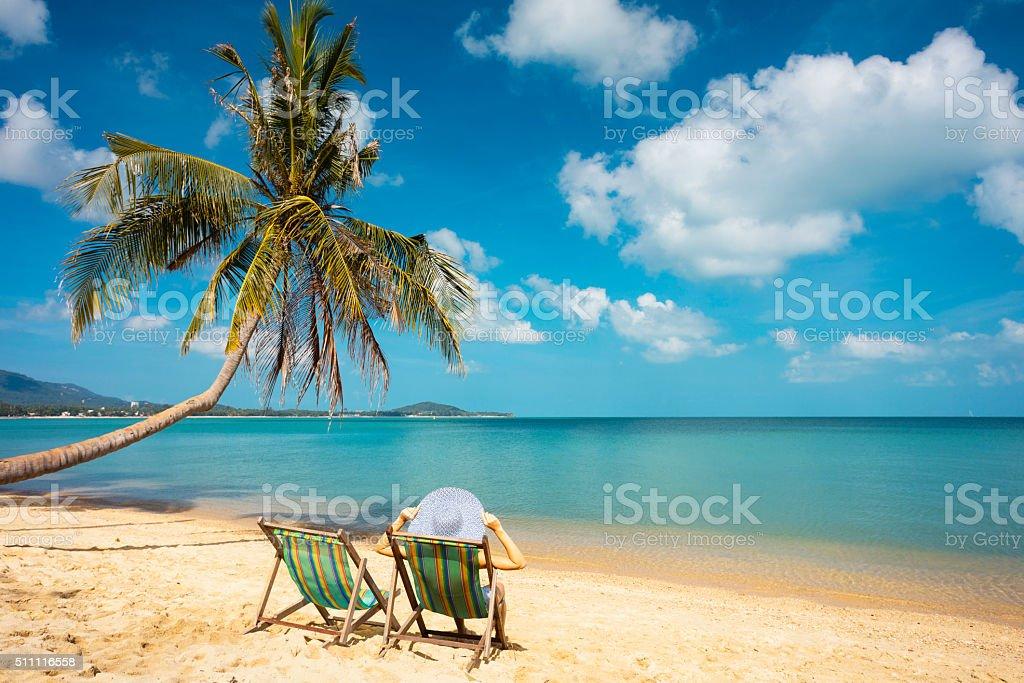 woman sunbathing in beach chair stock photo
